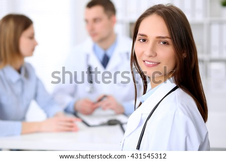 Young beautiful female doctor smiling  on the background with patient in hospital. High level and quality medical service concept.   - stock photo