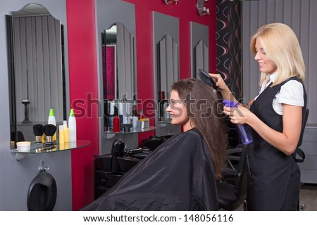 Young beautiful female hairdresser working in beauty salon - stock photo