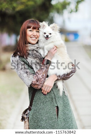 Young beautiful female holding her little puppy and smiling outdoors - stock photo