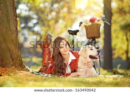 Young beautiful female lying on a green grass with her labrador retriever dog in a park - stock photo