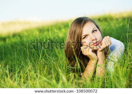 Young beautiful female relaxing in the grass