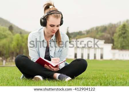 Young beautiful female sitting and writing outside while listening music on earphones as outdoor relaxation concept - stock photo