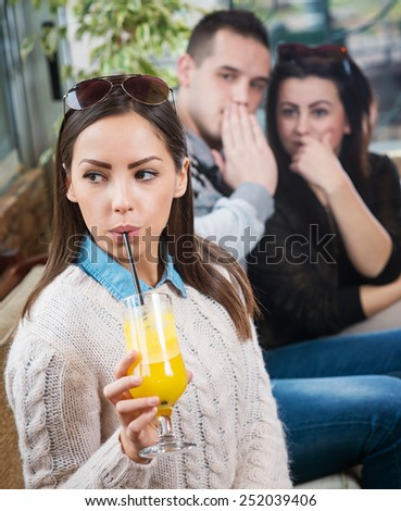 Young beautiful female sitting in cafe while the two gossiping behind. - stock photo