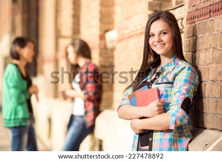 Young beautiful female student at the college, outdoors. Her classmates in the background. - stock photo