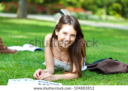 Young beautiful female student lying on the grass - stock photo