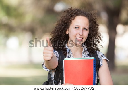 Young Beautiful Female Student with Thumb Up - stock photo