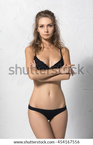 Young, beautiful, fit and sporty fashion woman posing in black lingerie or underwear on white textured wall, hands folded on the chest, looks like guard - stock photo