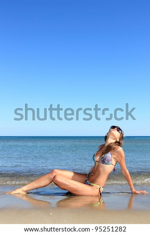 Young beautiful fit woman posing at the beach - stock photo