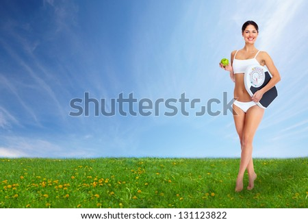 Young beautiful fitness woman. On blue sky background. - stock photo
