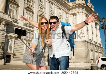 young beautiful friends tourist couple visiting Spain in holidays exchange students and taking selfie stick picture together in town happy on sunny day in travel and vacation concept - stock photo