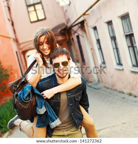 Young beautiful funny couple in love having fun outdoor on the street in summer - stock photo