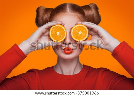 Young beautiful funny fashion model with orange slice on orange background. with orange makeup and hairstyle and freckles. holding orange between eyes with kiss. - stock photo
