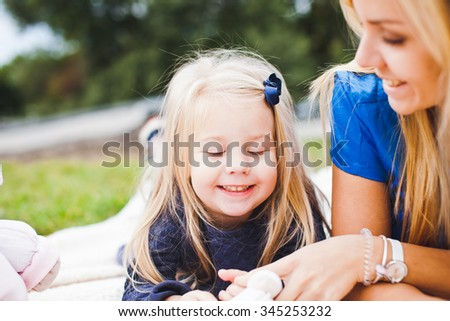 Young beautiful funny girl and her mom on picnic in park at sunny summer day relaxing outdoors. Both blonds. Emotion expressions on kid face. Little child fools at camera - stock photo