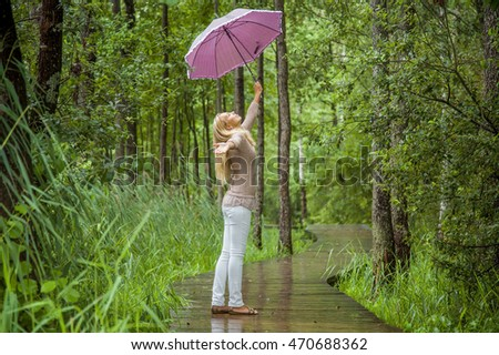 Young, beautiful, gentle woman with an umbrella walking in the park in rainy day and she enjoying the fresh air...