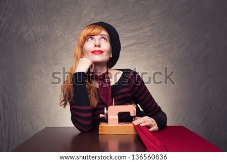 young beautiful ginger lady with retro clothes and a sewing machine dreaming on grunge background - stock photo