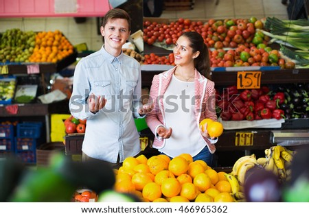 Young beautiful  girl and smiling boyfriend buying citruses in grocery store