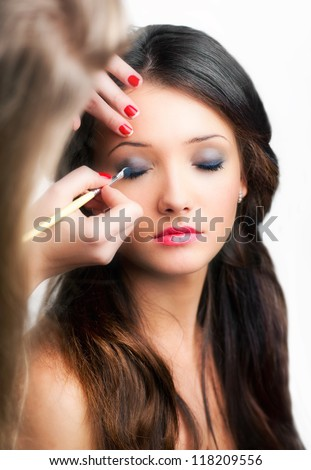 Young beautiful girl applying fashion make-up by make-up artist - stock photo