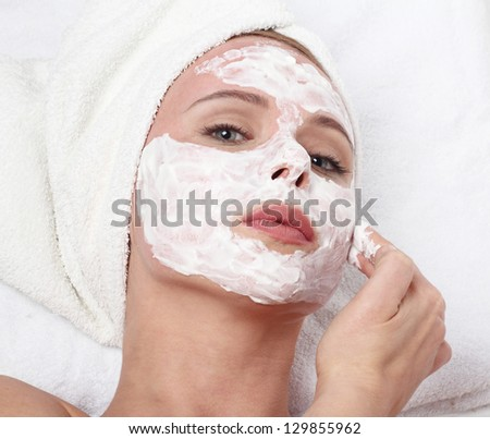 Young beautiful girl applying homemade facial mask i at home.Skin care, beauty treatments. - stock photo