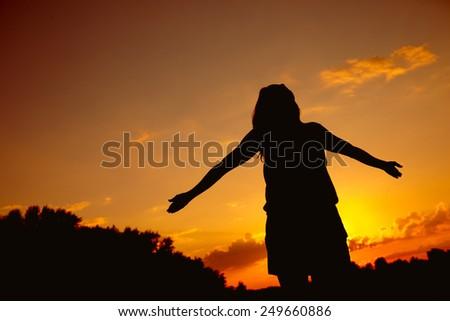 Young beautiful girl at sunset - stock photo
