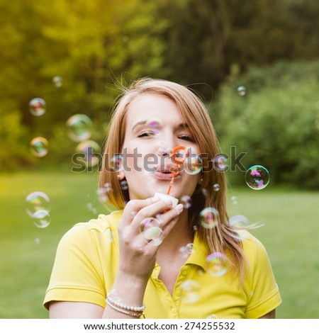 Young beautiful girl blowing bubbles summer outdoors.
