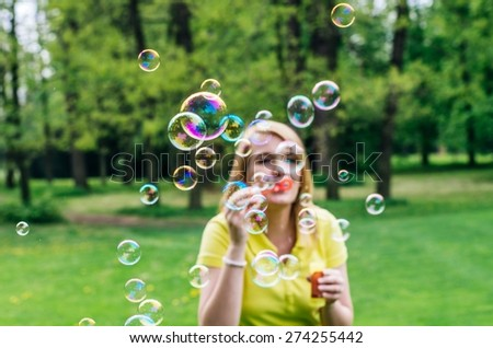 Young beautiful girl blowing bubbles summer outdoors.  Selective focus on bubbles. Blurred face. - stock photo