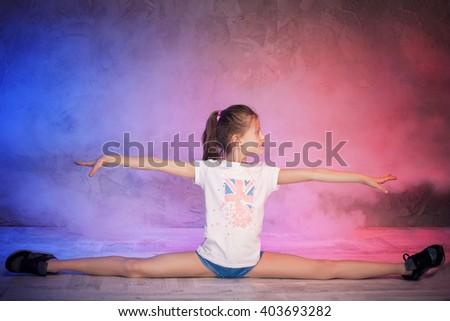 Young beautiful girl doing twine. Studio shot. - stock photo