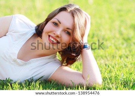 Young beautiful girl dreaming on green field