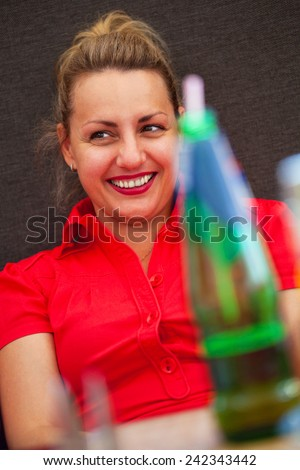 Young beautiful girl emotionally laughing in a cafe - stock photo