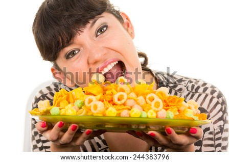 young beautiful girl enjoying eating junk food chips isolated on white - stock photo