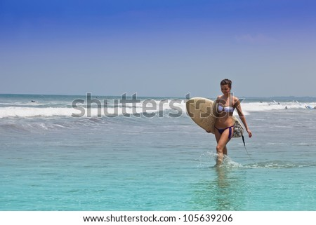 young beautiful girl goes to bikini on an ocean coast with a board for surf