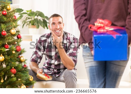 Young beautiful girl has a Christmas present for her boyfriend and she wants to surprise him. - stock photo