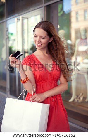 Young beautiful girl holding a blank credit card and shopping bag outdoor against store background - stock photo