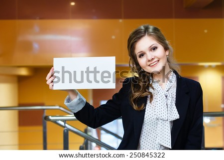 Young beautiful girl holding empty white card and smiling - stock photo
