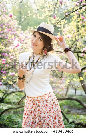 Young beautiful girl in a blossoming spring magnolia garden. The girl in the garden morning. Boho style. Portrait, close-up. The girl in the hat, necklace and earrings. - stock photo