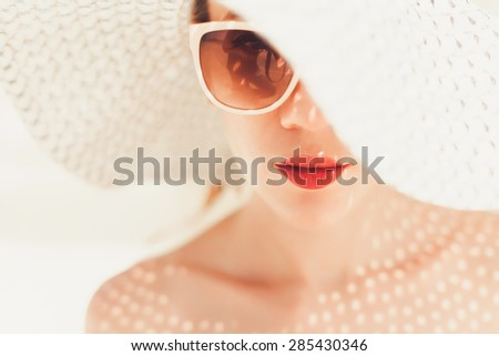 young beautiful girl in a large hat and sunglasses with red lips posing on the beach - stock photo