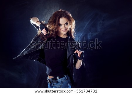 young beautiful girl in a leather jacket on the texture  background, rock style