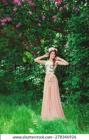 Young beautiful girl in a long dress and a wreath of flowers in the garden of lilac bush - stock photo