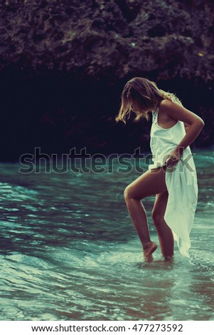 young beautiful girl in a long white dress on the beach among the rocks. woman in the ocean water in a white dress.