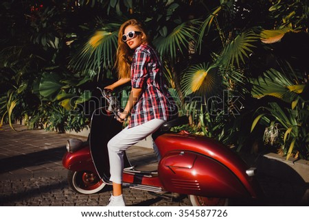 young beautiful girl in a red plaid shirt wearing sunglasses with red lipstick white jeans and sneakers posing on a red Vespa scooter near palm trees on the streets of Italy - stock photo