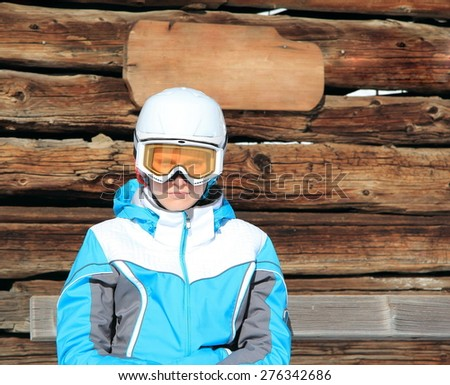 young beautiful girl in a ski suit, a mask and a white helmet on his head against the background of wooden wall - stock photo