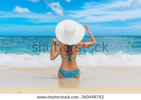 Young beautiful girl in a straw white hat back to the viewer on the beach of a tropical island. Summer vacation concept. - stock photo