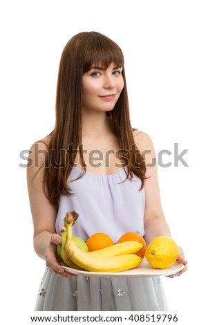 Young beautiful girl in a summer dress with a tray of fruits in her hands isolated on white background - stock photo