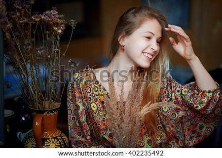 Young beautiful girl in a vintage dress posing in an old art Studio. The girl model poses in the Studio of an old artist. a young girl looks at flowers