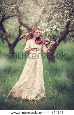 Young beautiful girl in a white dress under blossoming apple tree holding a violin in hands. Blooming spring. - stock photo