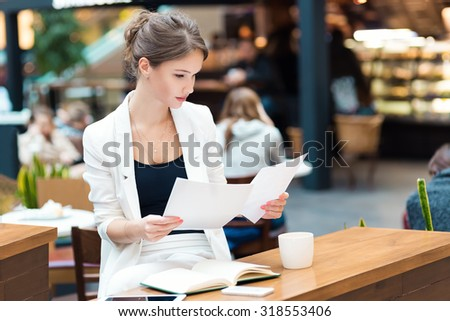 Young, beautiful girl in a white suit, sitting in the cafe at the business meeting - stock photo