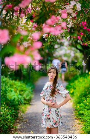 young beautiful girl in a white sundress standing near the tree with flowers