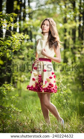 Young beautiful girl in a yellow dress in the woods. Portrait of romantic woman in fairy forest.  Stunning fashionable teenage model in summer meadow, outdoor shot. Cute brunette long hair female. - stock photo