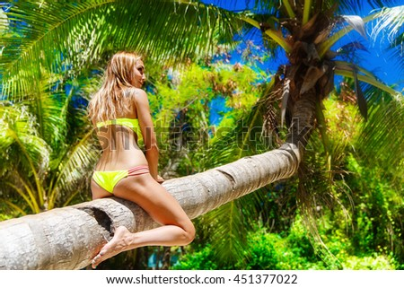 Young beautiful girl in bikini on the palm tree on a tropical beach. Sky and sea in the background. Summer vacation concept.