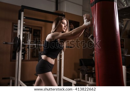 young beautiful girl in boxing bandage hit red bag left hand at gym