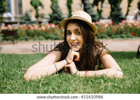 Young beautiful girl in hat lying on grass and looking happy - stock photo